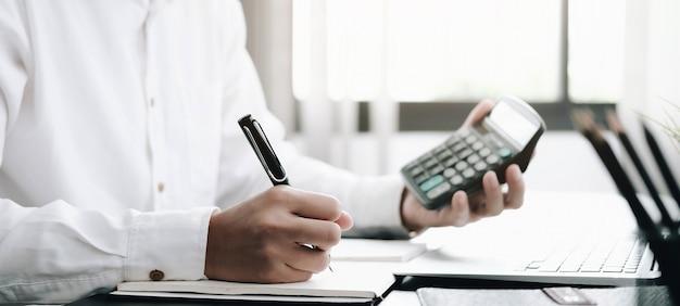 Homem de negócios usando calculadora para fazer finanças matemáticas em uma mesa de madeira no escritório
