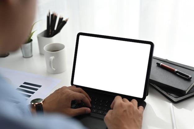 Homem de negócios usando computador tablet e analisando tabelas e gráficos no escritório.