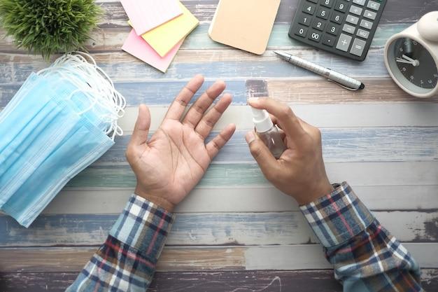 Homem de negócios usando gel desinfetante na mesa do escritório de cima para baixo