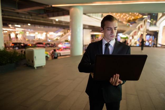 Homem de negócios usando laptop ao ar livre à noite na cidade