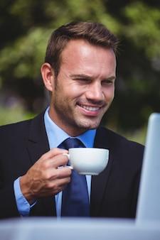 Homem de negócios usando laptop e tomando um café