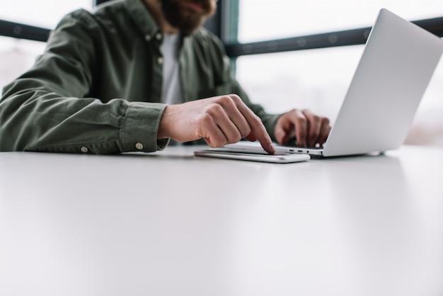 Homem de negócios usando laptop, telefone celular, internet, trabalhando no escritório