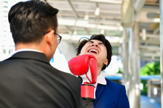 Homem de negócios usando luvas de boxe, jogando um soco.