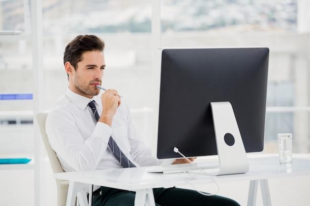 Homem de negócios usando o computador e tomar notas