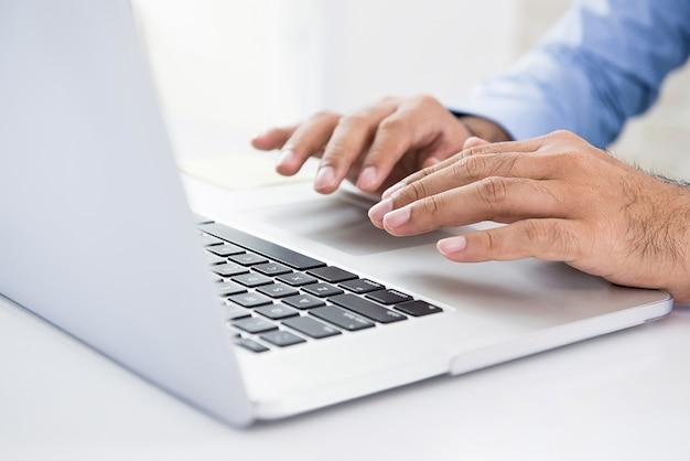 Homem de negócios usando o computador portátil, trabalhando e procurando informações