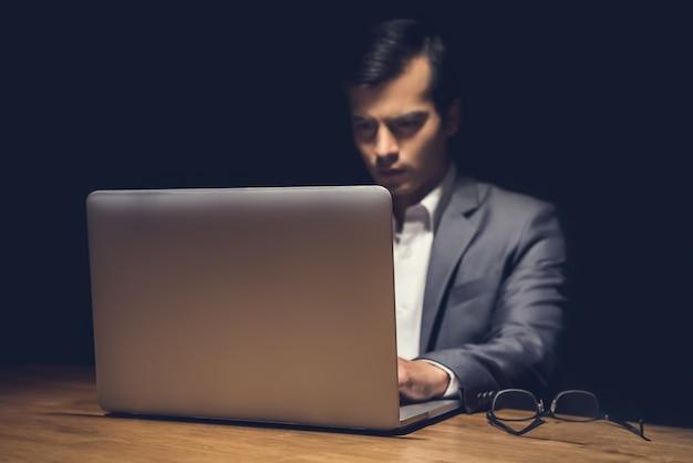 Homem de negócios usando o computador portátil trabalhando tarde da noite no quarto escuro