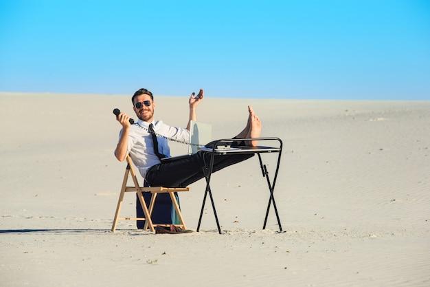Homem de negócios usando o laptop no deserto