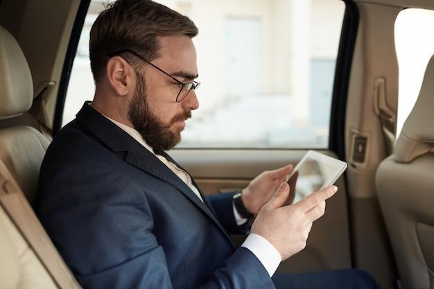Homem de negócios usando o tablet pc no carro