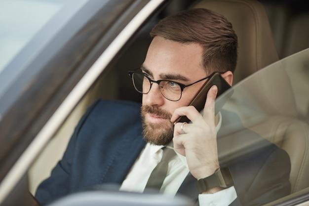 Homem de negócios usando o telefone durante a condução