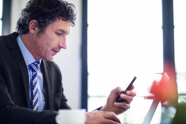Homem de negócios usando o telefone enquanto trabalhava no laptop