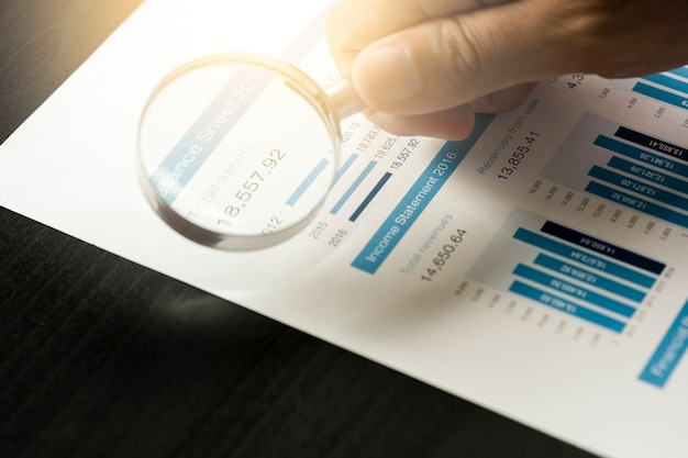Homem de negócios usando o vidro da lupa para análise de dados financeiros e encontrar a melhor empresa do mercado de ações. investidor de valor