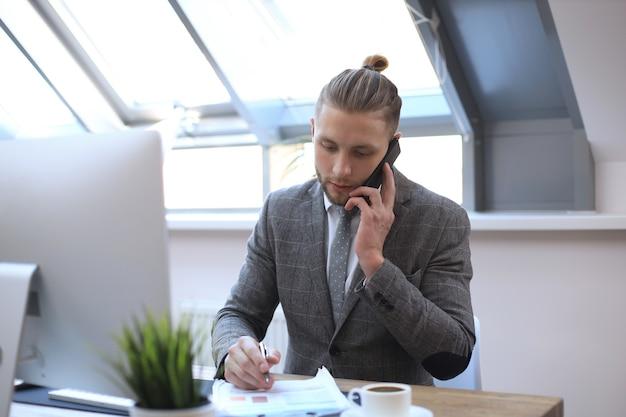Homem de negócios usando seu telefone celular no escritório.