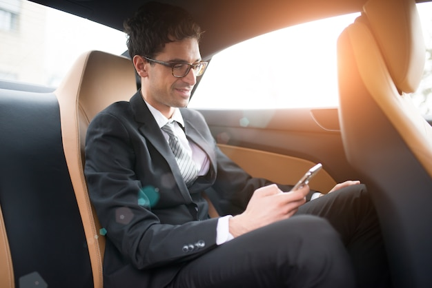 Homem de negócios usando seu telefone móvel no banco de trás de um carro
