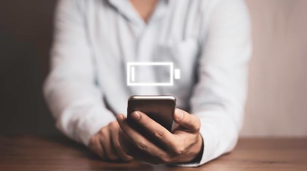 Homem de negócios usando smartphone com ícone de bateria fraca.