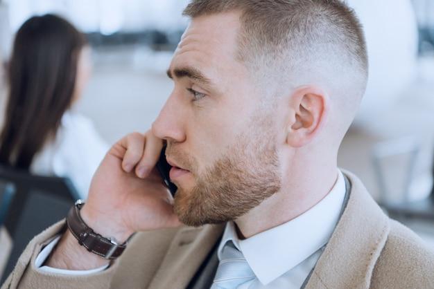 Homem de negócios usando smartphone dentro de prédio de escritórios ou aeroporto.