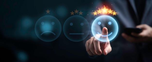 Homem de negócios usando smartphone e empurrando o botão de sorriso para a melhor avaliação e excelente classificação dos clientes, conceito de satisfação do cliente.