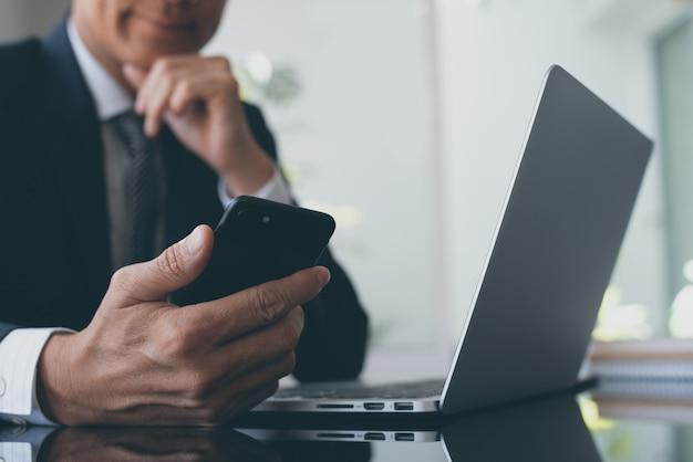 Homem de negócios usando smartphone enquanto trabalhava no computador portátil no escritório