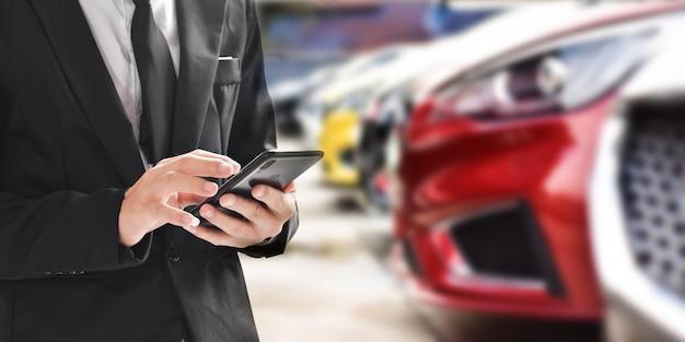 Homem de negócios usando smartphone no fundo desfocado do carro novo, exibido no revendedor de sala de exposições com espaço de cópia.