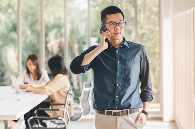 Homem de negócios usando smartphone para discutir o plano de negócios na sala de reuniões