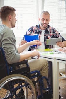 Homem de negócios usando tablet digital com colega de handicap