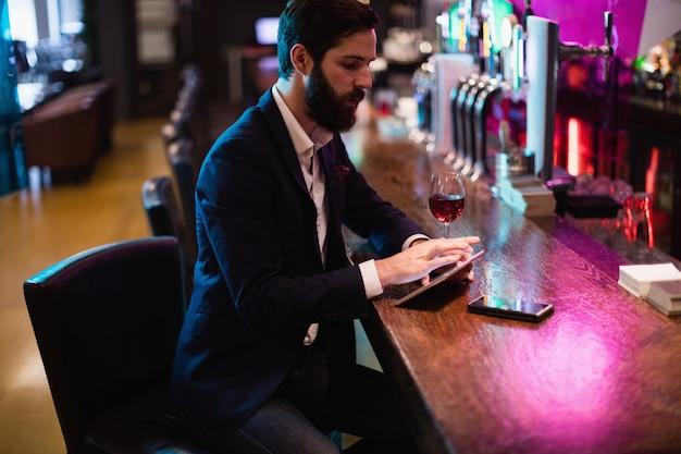 Homem de negócios usando tablet digital com copo de vinho e telefone celular no balcão