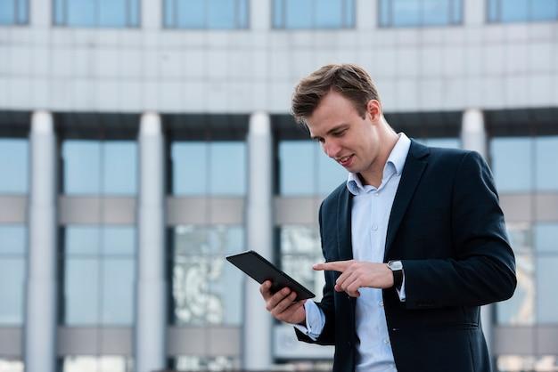 Homem de negócios usando tablet perto de prédio