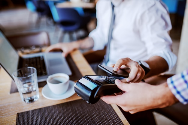 Homem de negócios usando tecnologia de pagamento móvel para pagar a conta na cafeteria.