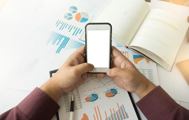 Homem de negócios usando tela branca em branco do smartphone. trabalhando no escritório com documentos em sua mesa.