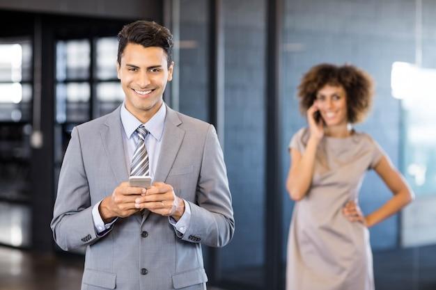 Homem de negócios usando telefone celular com uma mulher sorridente