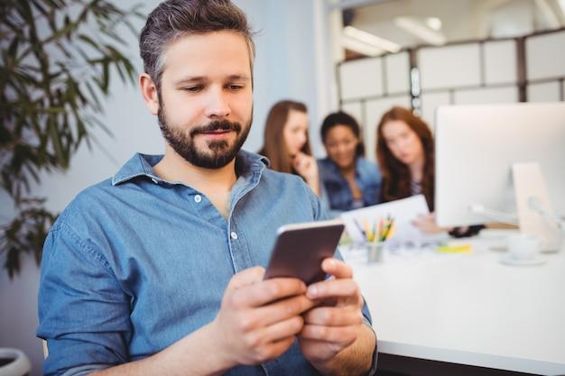 Homem de negócios usando telefone celular contra colegas de trabalho do sexo feminino