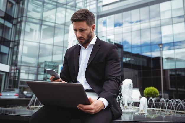 Homem de negócios usando telefone celular e laptop
