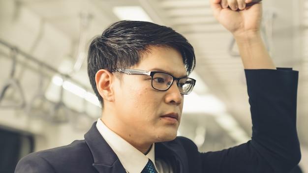 Homem de negócios usando telefone celular em trem público. conceito de deslocamento diário do estilo de vida urbano da cidade.
