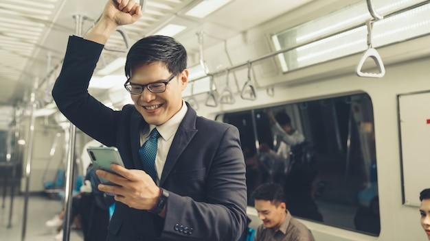Homem de negócios usando telefone celular em trem público