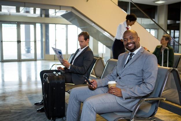 Homem de negócios usando telefone celular na área de espera do terminal do aeroporto