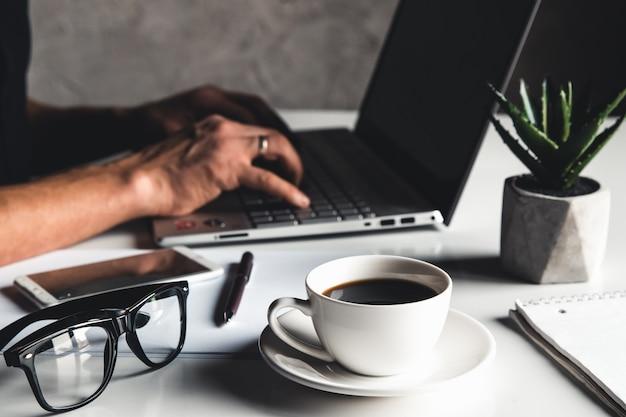 Homem de negócios usando um laptop e digitando no teclado do laptop com óculos de caneta e uma xícara de café quente