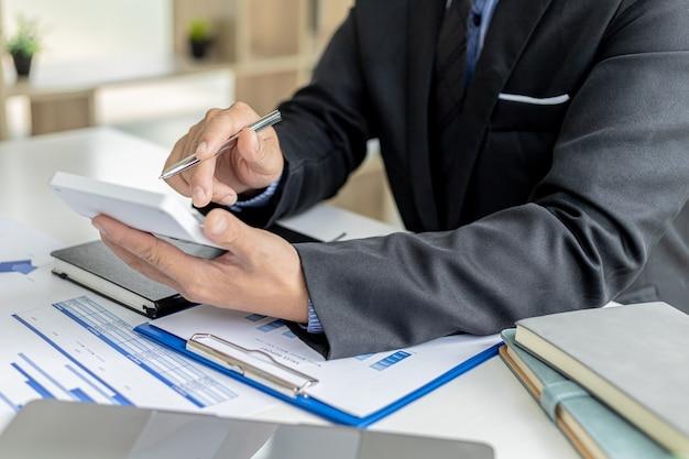 Homem de negócios usando uma calculadora para calcular números nos documentos financeiros de uma empresa, ele está analisando dados financeiros históricos para planejar como fazer a empresa crescer. conceito financeiro.
