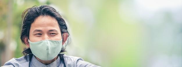 Homem de negócios usando uma máscara de pano em área pública se proteger do risco de doença