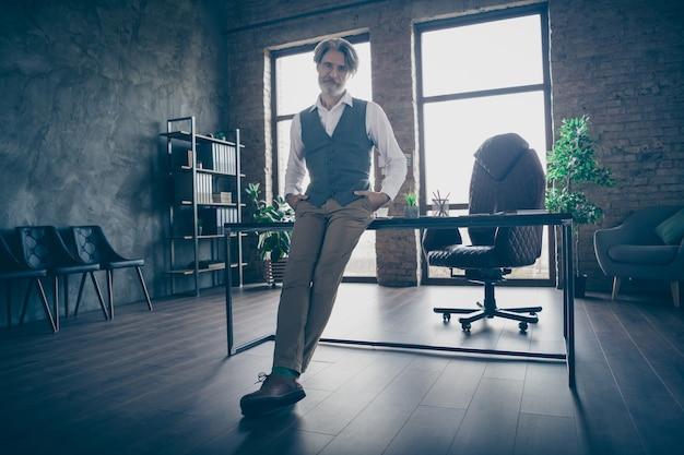Homem de negócios velho e confiante em pé no escritório com as mãos nos bolsos