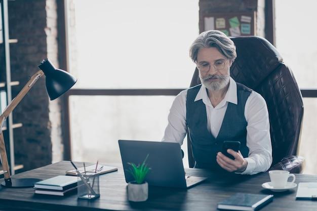 Homem de negócios velho e inteligente sentar na mesa, trabalhar no laptop e usar o smartphone no escritório