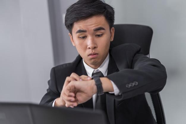 Homem de negócios, verificando o tempo no relógio enquanto estiver usando o laptop