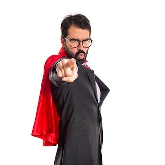 Homem de negócios vestido como super-herói apontando para a frente