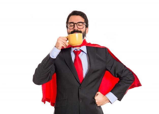 Homem de negócios vestido como super-herói bebendo café