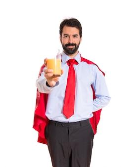 Homem de negócios vestido como super-herói com suco de laranja