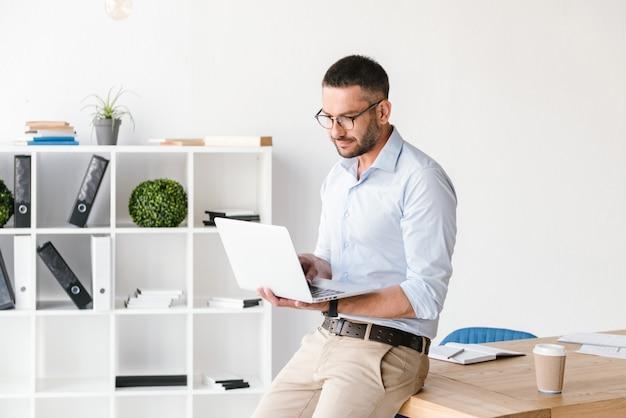 Homem de negócios, vestindo uma camisa branca, sentado na mesa do escritório e usando um laptop prata para trabalhar