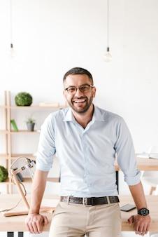Homem de negócios, vestindo uma camisa branca, sentado na mesa do escritório, sorrindo para a câmera