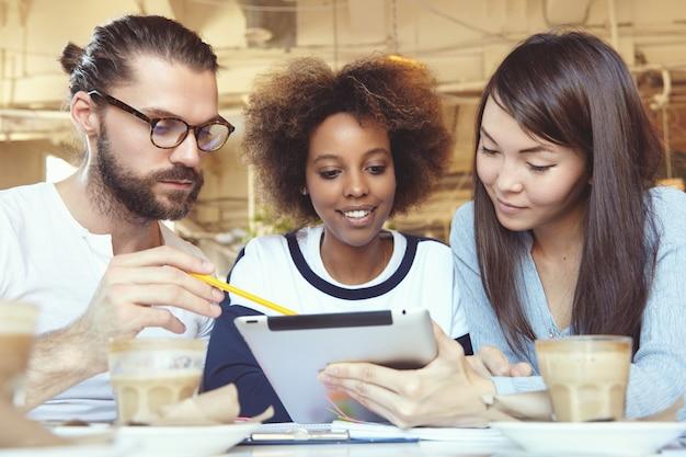 Homem de óculos apresentando estratégia de negócios no tablet pc, mostrando informações na tela com lápis, enquanto seus colegas asiáticos e africanos o ouvem com atenção, sentados em um espaço de trabalho compartilhado