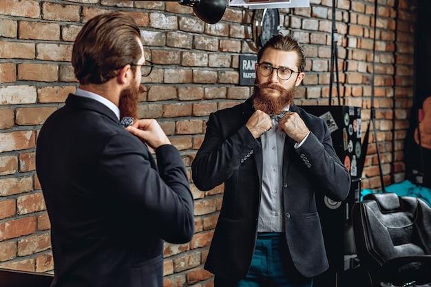 Homem de óculos, barba e bigode, olhando-se no espelho e endireitando uma gravata borboleta no colarinho