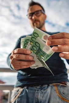 Homem de óculos, camisa azul. e segurando a pilha de dinheiro.