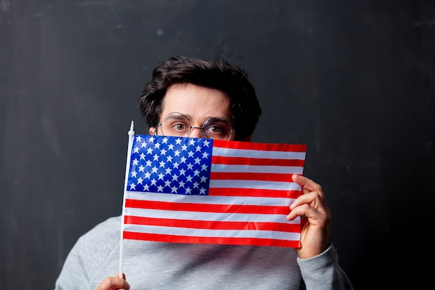 Homem de óculos com bandeira eua em fundo escuro