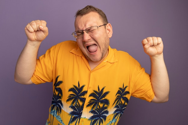 Homem de óculos com camisa laranja cerrando os punhos loucamente feliz gritando em pé sobre a parede roxa
